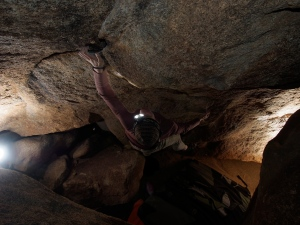 crux of Librian Underground, v3. This problem sits at the bottom of boulder piles just over the dry waterway.